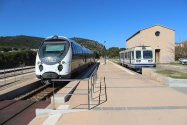 A modern and an older train at the station